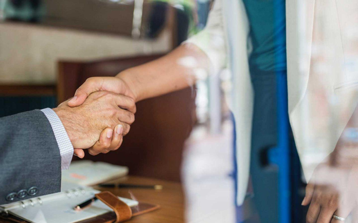 close up photo of a business man and woman's hands shaking