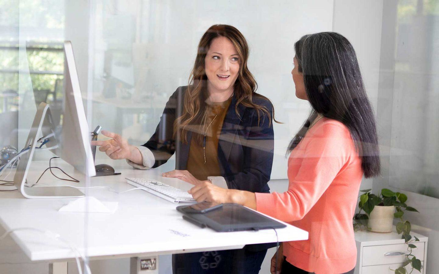 woman in pink shirt and woman in blazer working together at a white desk in front of a computer