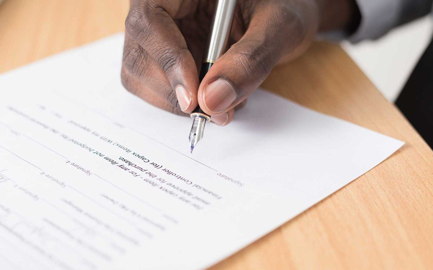 close up photo of a man's hand holding a pen and signing a document
