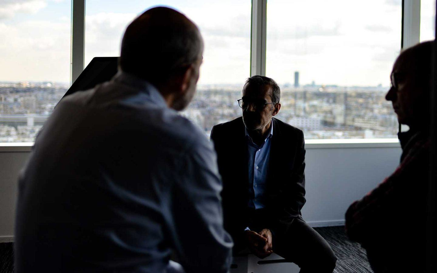 three people sitting in conversation in an office