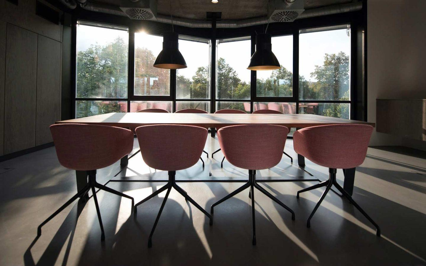 a meeting table with eight pink chairs in a loft style meeting room